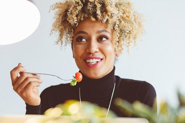 Woman eating a cherry tomato and lettuce to maintain a healthy office lifestyle while smiling and looking away.
