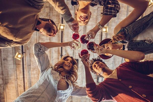 Low angle view of happy young colleagues working in a start up team toasting to their success.