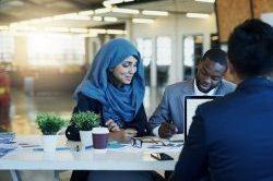 Shot of a diverse group of businesspeople, two men and a woman in a hijab, working together in an office in Dubai.