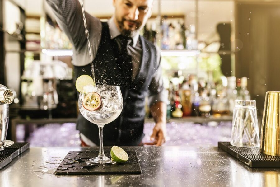 A West End barman mixes a cocktail in a hospitality establishment