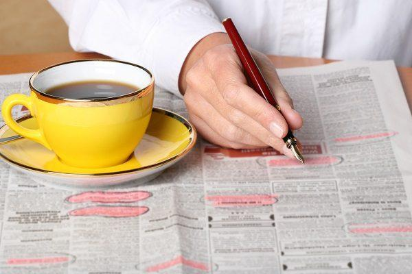 A person's hand using a pen and highlighter circling job ads in a newspaper. There's a coffee sitting on the table.
