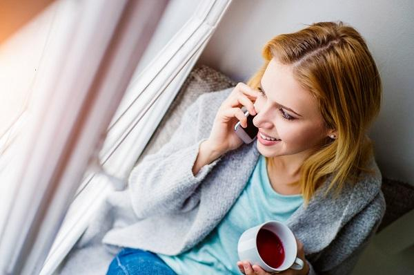 A close up on a woman in loungewear, holding a cup of tea and talking on a mobile phone while looking out a window.