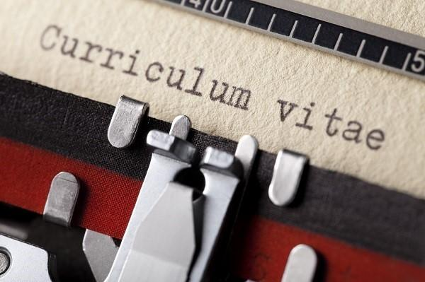 Close up on a typewriter that's typed curriculum vitae on a piece of paper.