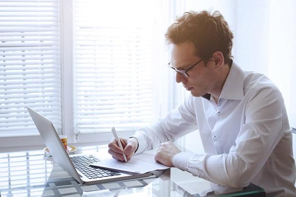 A man with tousled hair and glasses using a laptop and taking notes on a desk, searching for a job in a tough market.
