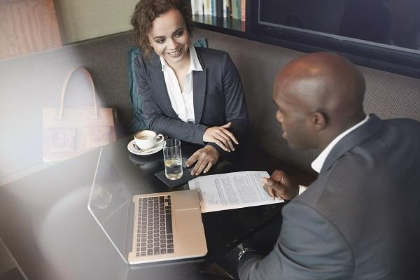 A woman and a man at a table in a coffee house, having a meeting. One of them is a recruitment consultant.