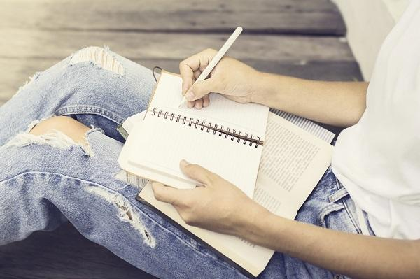 A woman holding a book and a notebook in her lap. She's writing notes and constructing a successful CV.