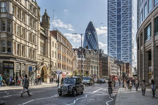A shot of the financial district in the City of London, with a black cab, the Gherkin and people walking along the footpath.