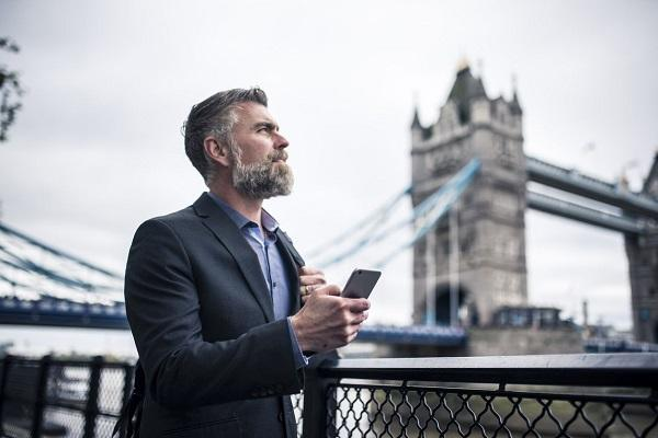 A business man with a grey beard talking on the phone while leaning on a railing next to the Thames in London.