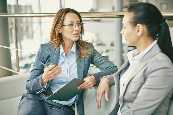 A woman being coached on her career in an open plan office by another woman wearing glasses and holding a clipboard.