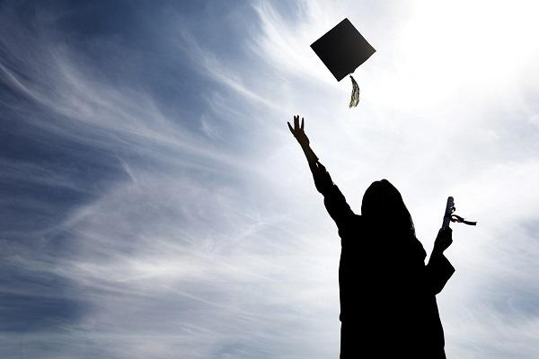 A black shadow of a graduate throwing their hat up into the air with a degree and sunny background.