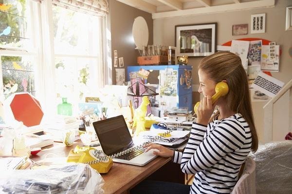 A woman in a flexible working arrangement using a yellow landline phone in a sunlit home office.