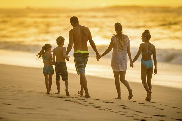 A family of five walking along a beach at sunset, with the parents taking all of their holiday entitlement.