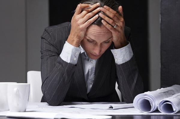 A man in a business suit looking over papers and attempting to keep on top of his workload.