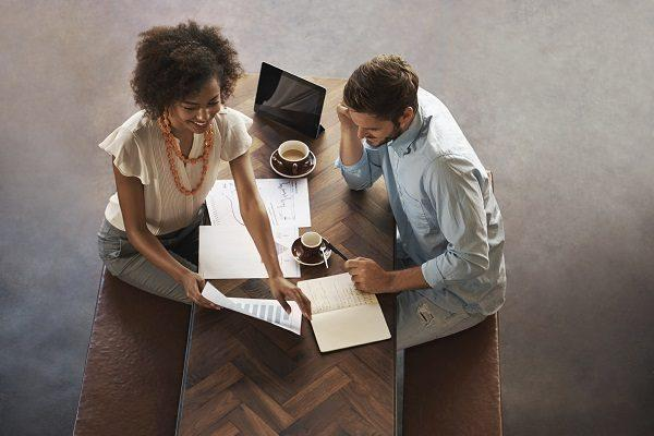 An overhead shot of two colleagues having a business meeting in a hip, open plan office.