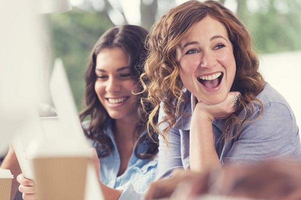 Two smiling women in business wear in an office meeting room.