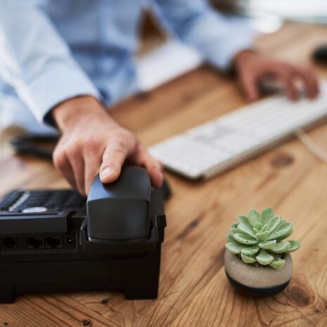 Cropped shot of a man holding the receiver of a telephone in a virtual office with a cactus on the desk.