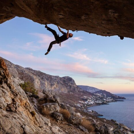 Male climber climbing along roof in cave at sunset with pink clouds against beautiful view of coast below.