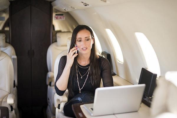 A secretary on a private plane talking on the phone and using a laptop computer.