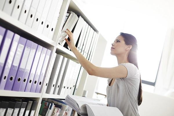 A secretary in an organised office room searching for a document of folders on a shelf.