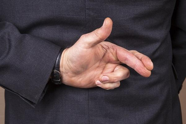 A business man's hands in a 'crossed fingers' sign held behind his back.