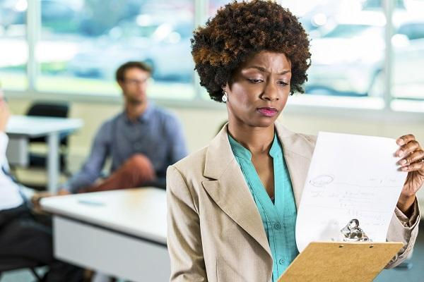 A business woman holding a clipboard and looking disappointed after an unsuccessful interview.