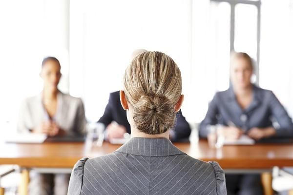 A woman sitting at a panel interview, presenting herself professionally in business wear.