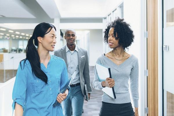Two women walking down a hallway in a workplace with their male colleague walking behind them.