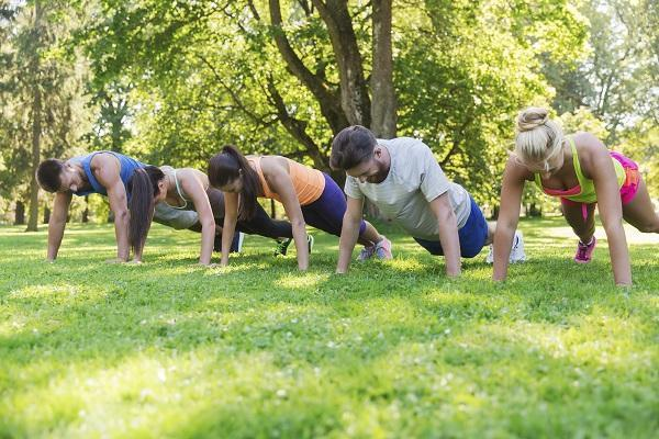 Five people exercising in the park together during work.