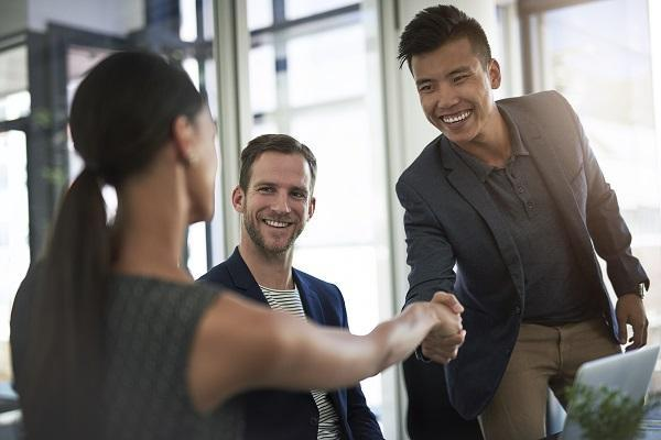 Three business people sit at a desk and shake hands, attracting the right candidates.