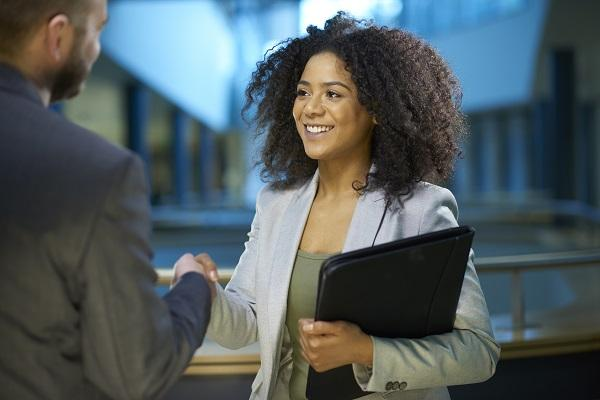 A hiring manager is shaking hands with a colleague while standing in an office building and holding papers.