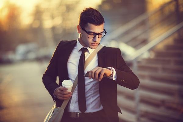 Man in a business suit in glasses looking at his watch while holding a coffee, running late for his job interview.