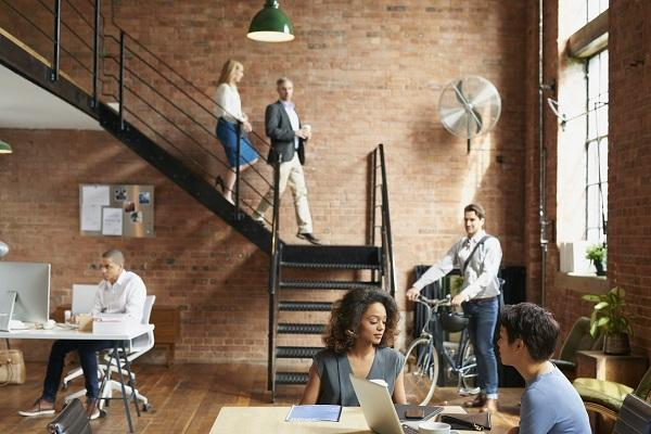 An open plan office with exposed brick walls and colleagues working in groups, symbolising a positive work culture.