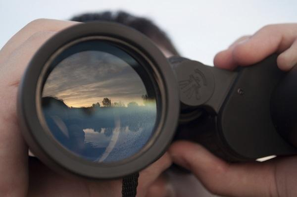 A close up on a man holding binoculars looking out on a lake at sunset.