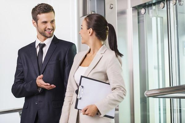 A man talking to his female colleague about his elevator pitch outside an elevator in their office.