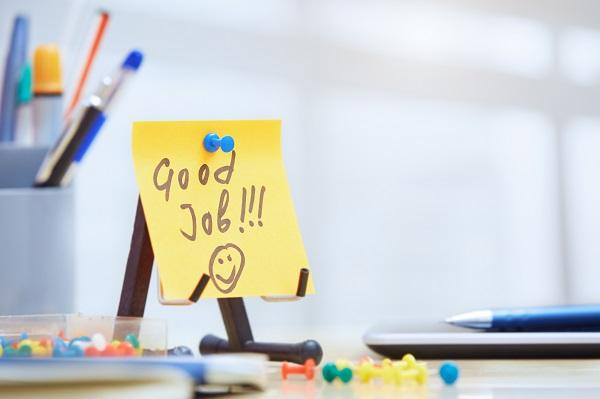 A post it note that says 'good job' with a smiley face on a desk with pens and thumb tacks spilt on the surface.