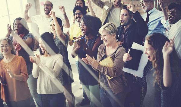 A group of people cheering, clapping, laughing and smiling in an office.
