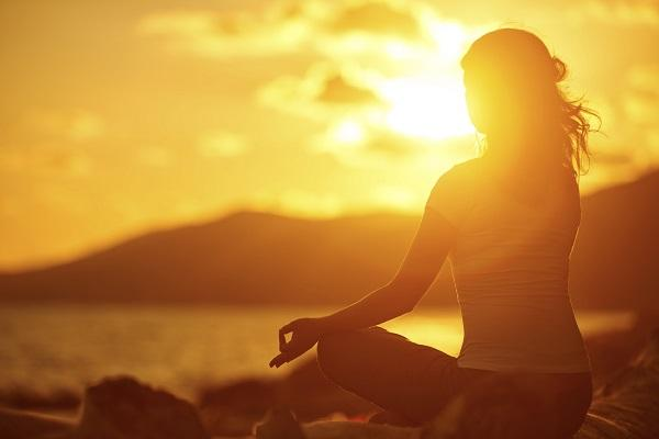A woman in a relaxing yoga pose sitting on the beach in the sunset.