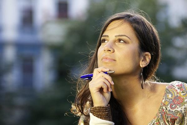 A woman holding a pen and looking off into the distance while thinking about settling into a new role.