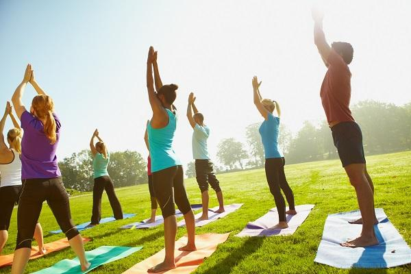 An outdoor yoga class in a park on a sunny day with eight participants.