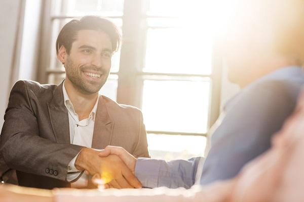 A chosen candidate shaking hands with an employer in a sunlit office.