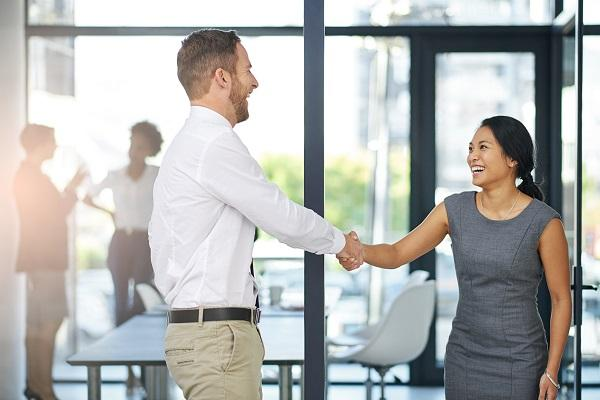 A successful recruiter shakes hands with her candidate in the foyer of a sunlit office.