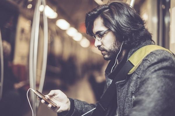 A man on public transport with headphones in and looking at his phone while researching into his employer.