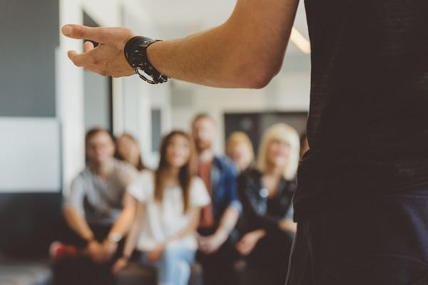 Image of a man at the front of a room with a crowd in a training seminar for administrative staff.