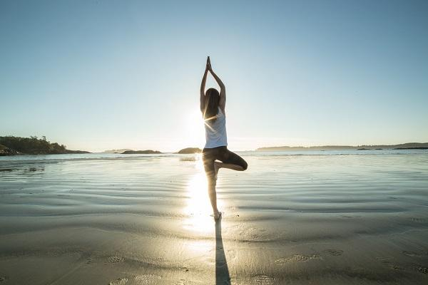 A private PA practicing yoga on a beach at sunset.