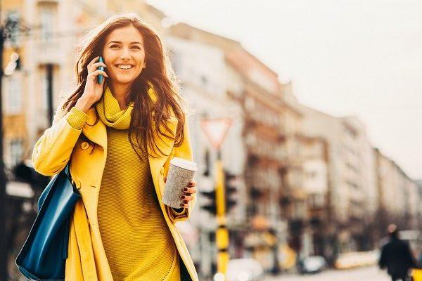 A PA in London in a yellow dress and coat smiling and talking on the phone while holding coffee and a handbag.