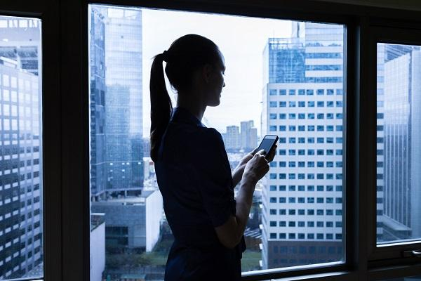 A woman uses a mobile phone to search for jobs while standing near a window, looking out at a city skyline.