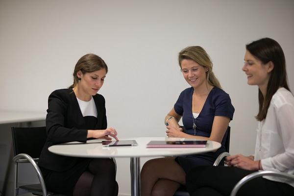Three recruitment consultants sitting around a table discussing the benefits of temp work.