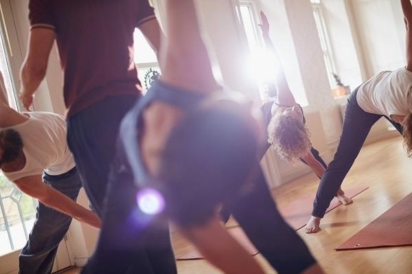 A group of people stretching in a yoga class with an instructor helping perfect the stretch.