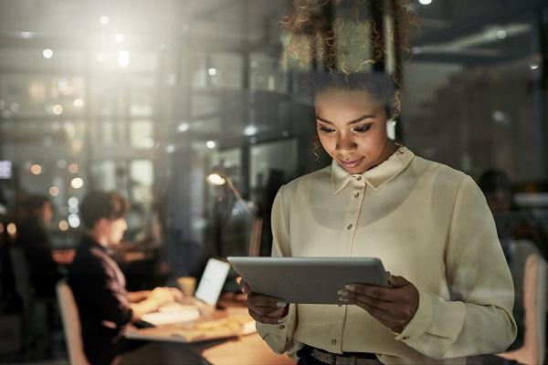 A private PA using an iPad in the foreground while her colleagues work in the background of an office at night.