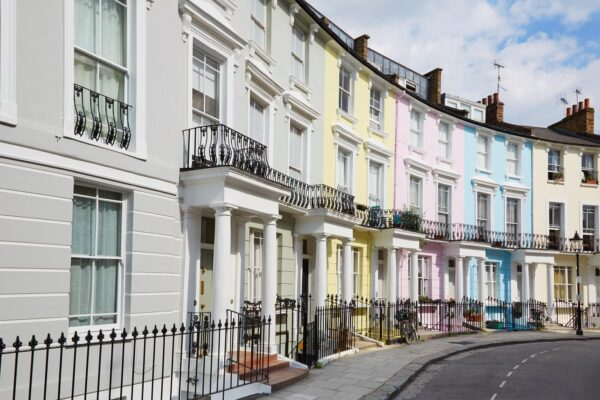 Colourful private London houses in Primrose hill lined up. They are painted grey, yellow, pink, blue and beige.